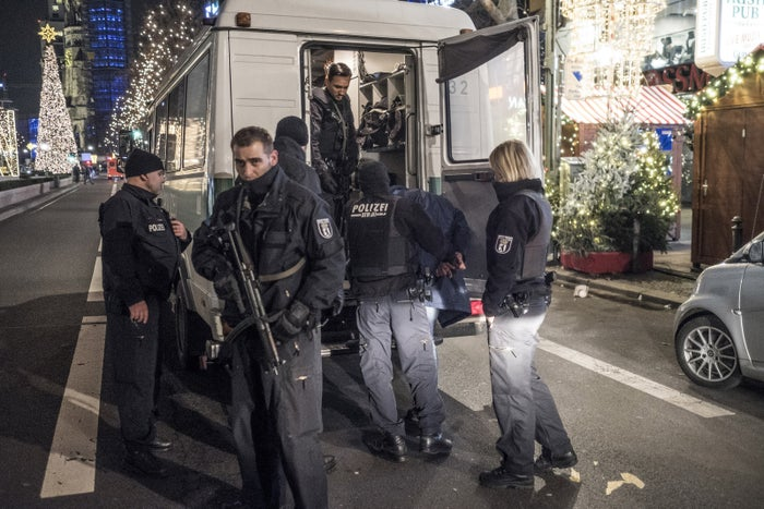 Police officers take a suspect into custody near the Christmas market at Breitscheidplatz in Berlin.