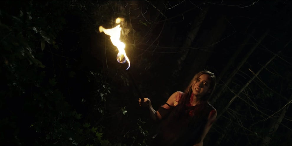 Zoe Kazan carrying a torch out into the dark in The Monster