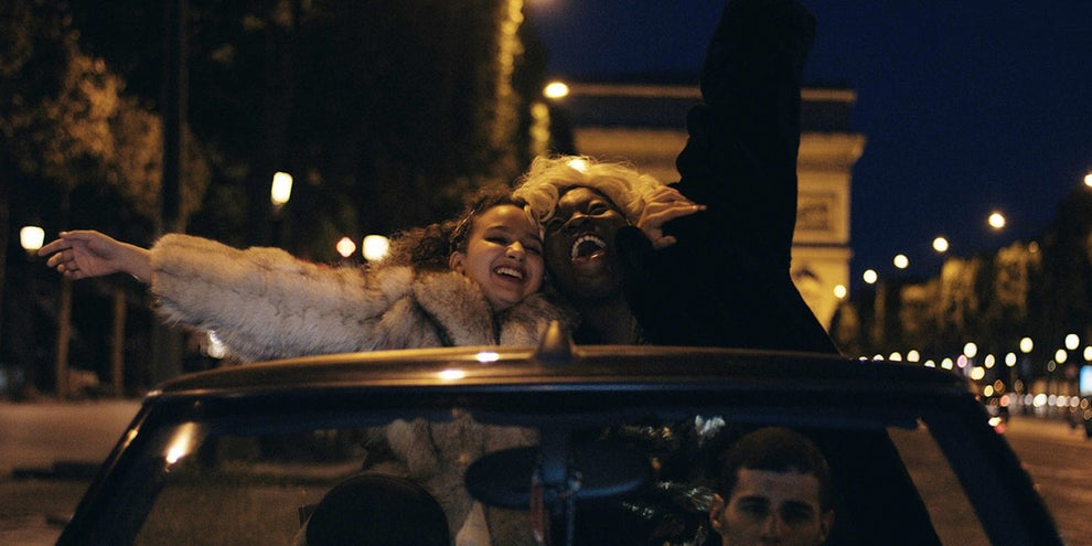 Dounia and Maimouna riding through Paris with the top down in Divines