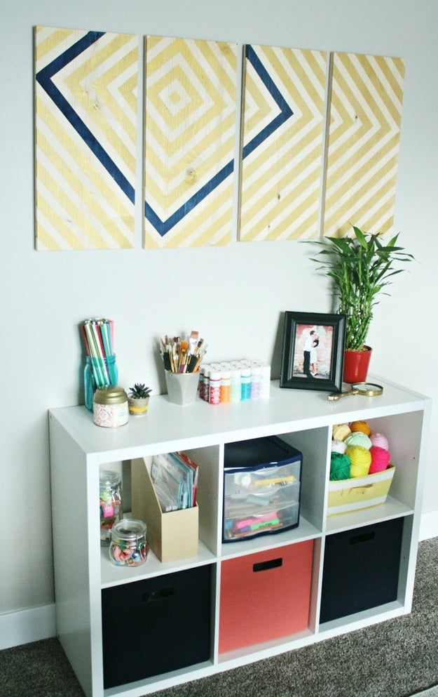 Craft your own geometric wall art with wood boards, painter's tape, and craft paint.