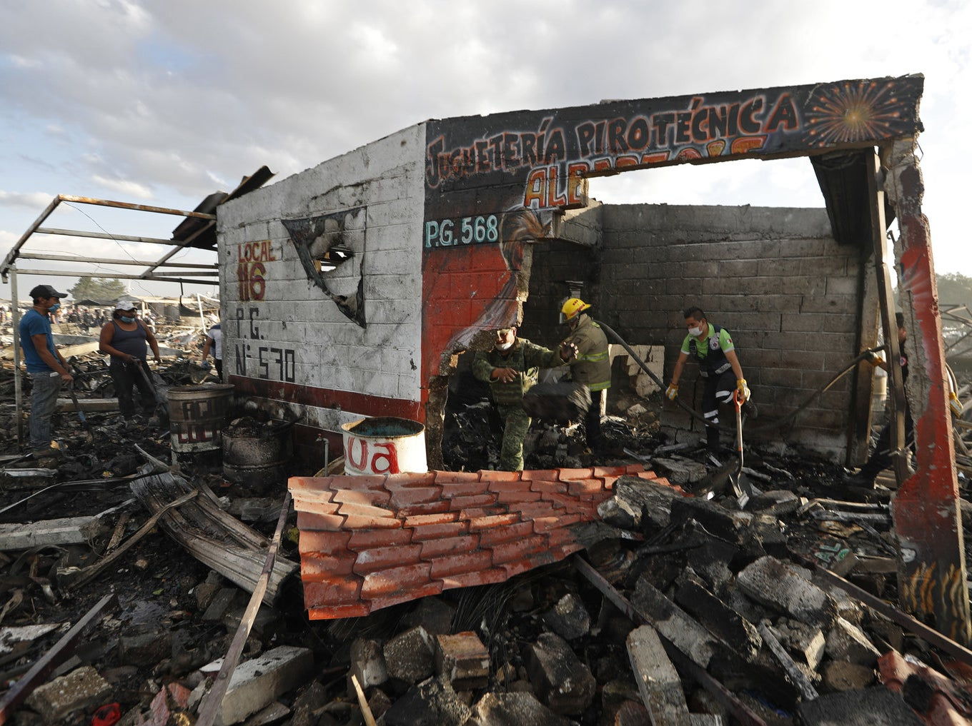 Firefighters and rescue workers search the charred ruins of the open-air market.