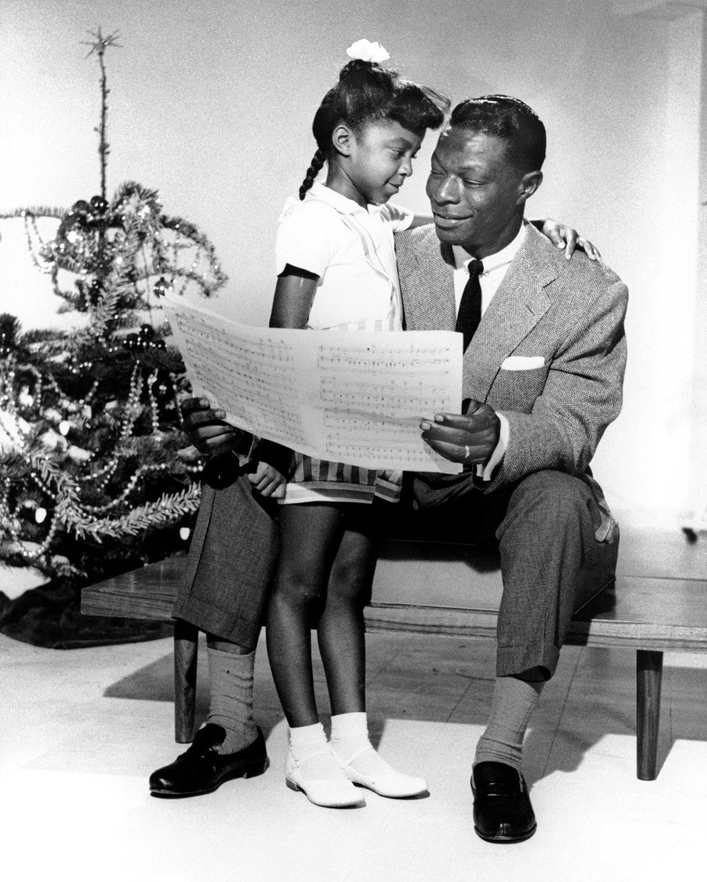 Nat King Cole sharing a tender holiday moment with his daughter Natalie in 1955.