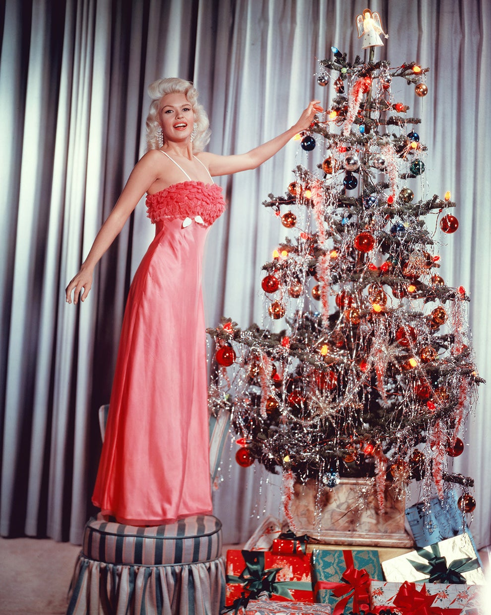 The glamorous Jayne Mansfield placing the angel topper on her Christmas tree in 1960.