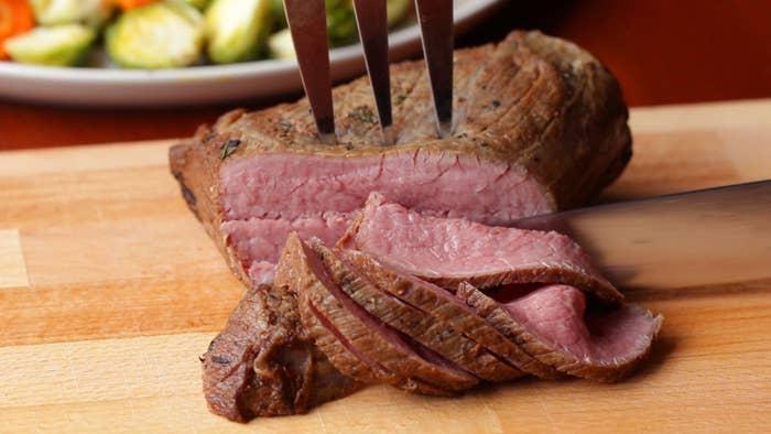 3−4人分材料:牛もも肉 450g オリーブオイル 大さじ1すりおろしにんにく 2片分 ローズマリー 大さじ1塩 小さじ1コショウ 適量サラダ油 大さじ1玉ねぎ 1/4個トマトペースト 大さじ1赤ワイン 200ml無塩バター 大さじ1作り方1.牛肉は冷蔵庫から出して30分程度置き、常温に戻す。オリーブオイルを表面にぬり、にんにくをすりこむ。塩、コショウ、ローズマリーをまんべんなくまぶす。2.フライパンにサラダ油を入れて強火で熱し、牛肉を焼く。表面のすべての面に焼き色がついたら、触れられる程度まで冷ます(約5分)。ジップ付きの袋に入れ、空気を抜く。フライパンはそのままにしておく。3.炊飯器にお湯1リットル、水200mlを入れ、温度計を入れて65℃まで冷ます。袋に入れた牛肉を入れて皿などで重しをし、肉全体が湯に浸かるようにし、保温する。(35分)4.ソースを作る。牛肉を焼いたフライパンに玉ねぎを入れ、弱火で炒める。あめ色になったらトマトペーストと赤ワインを入れて中火にし、とろみがつくまで煮立たせる。日を止めてバターを入れて溶かす。5.炊飯器から牛肉を取り出し、常温で30分程度冷ます(切り分ける前なら、冷蔵庫で3日ほど日持ちする)。6.(5)をなるべく薄く切り、(4)のソースをかけたら、完成!