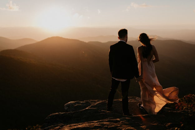 Just a flawless couple enjoying a sunset on a cliff.
