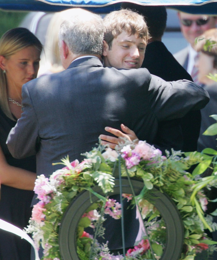 John Ramsey hugs his son, Burke, facing camera, at the graves of his wife, Patsy, and daughter JonBenet, in 2006.