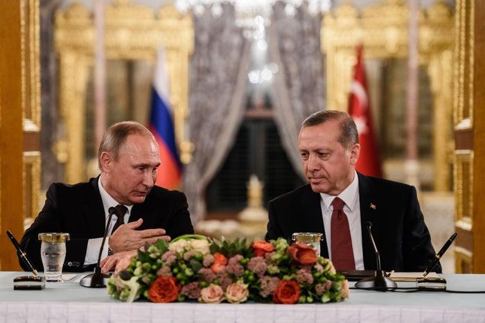 Russian President Vladimir Putin (L) speaks to Turkish President Recep Tayyip Erdogan
