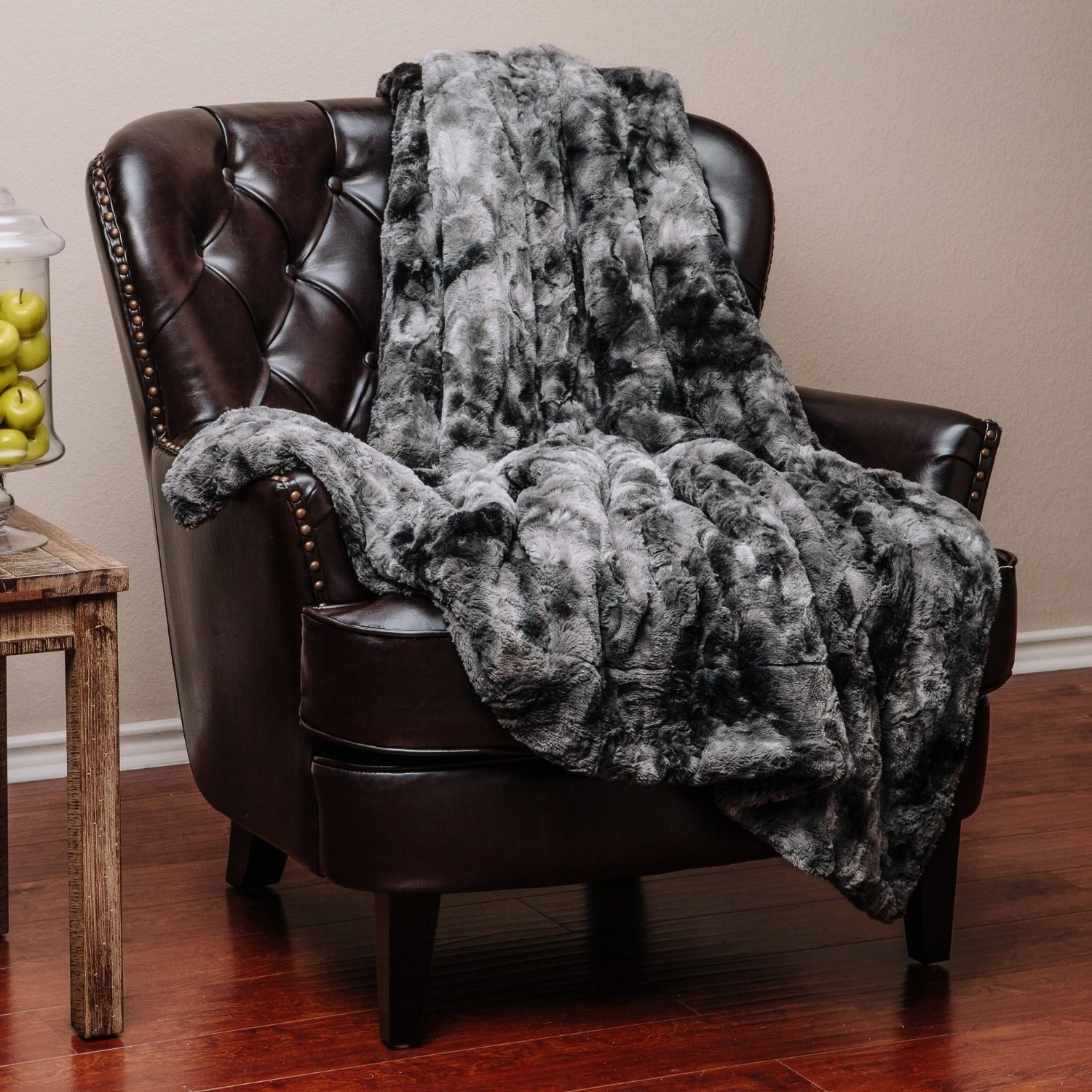 leather arm chair with faux fur gray blanket on it