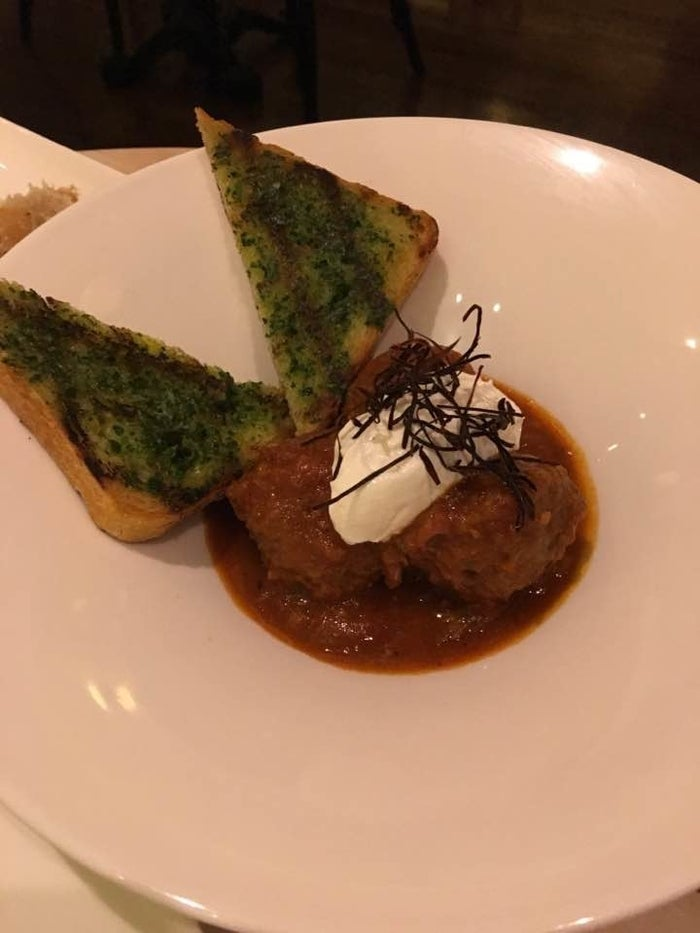 The dish includes three succulent lamb meatballs with Mediterranean spices and chickpeas topped with creamy labneh. It is served with grilled toast to dip in the savory smoked tomato jus.