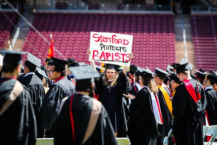 A woman carries a protest sign during graduation at Stanford University in June 2016.