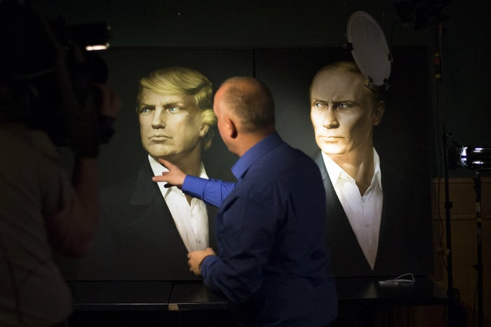 A journalist pointing at portraits of Trump and Putin during a live telecast of the US presidential election in Moscow.