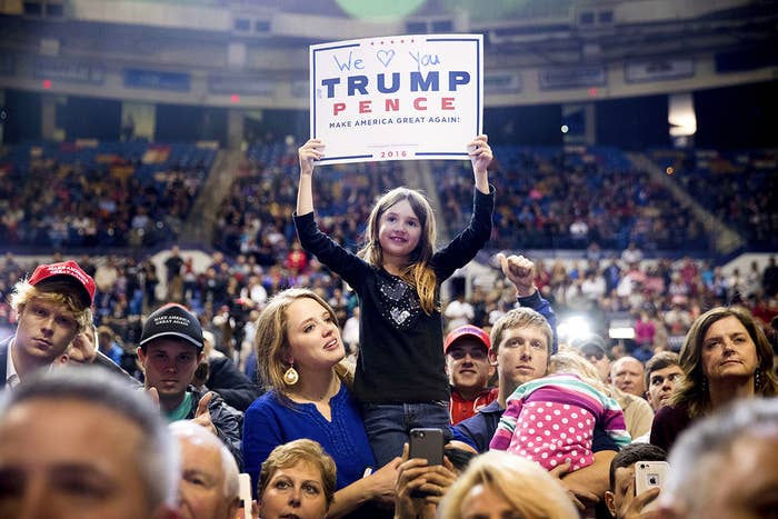 A girl holds up a campaign poster as President-elect Donald Trump speaks at a rally at the Crown Coliseum in Fayetteville, North Carolina.