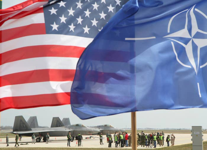 The US and NATO flags fly in front of two US Air Force F-22 Raptors in Lithuania.