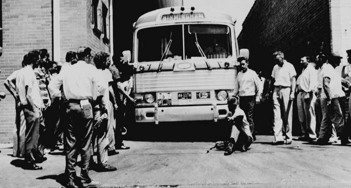 One unidentified white man sits in front of Greyhound bus to prevent it from leaving the station with a load of Freedom Riders in 1961.