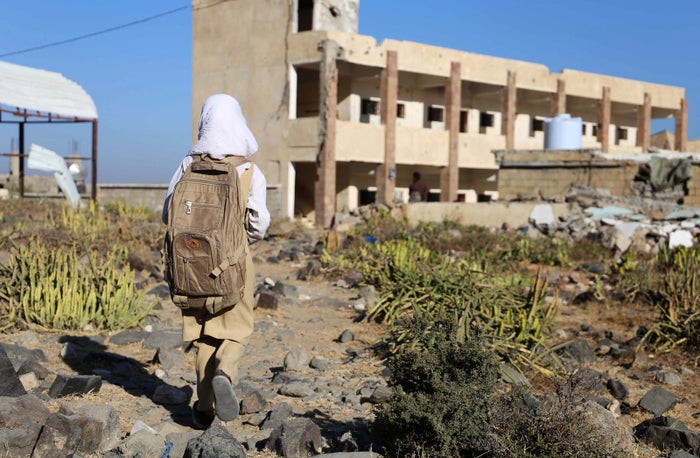 A Yemeni girl walks past a damaged building recently hit by a Saudi-led airstrike in the city of Taez.
