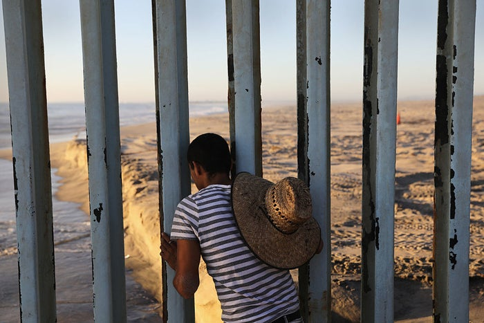 A man looks through the US–Mexico border fence from Tijuana.