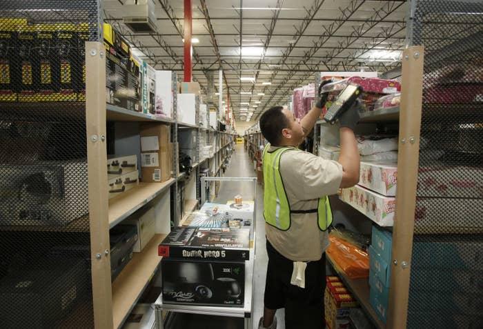 Shipment picker Marcus Marintez of Phoenix pulls items for shipment inside the 800,000 sq. ft. Amazon.com warehouse in Goodyear, Arizona.
