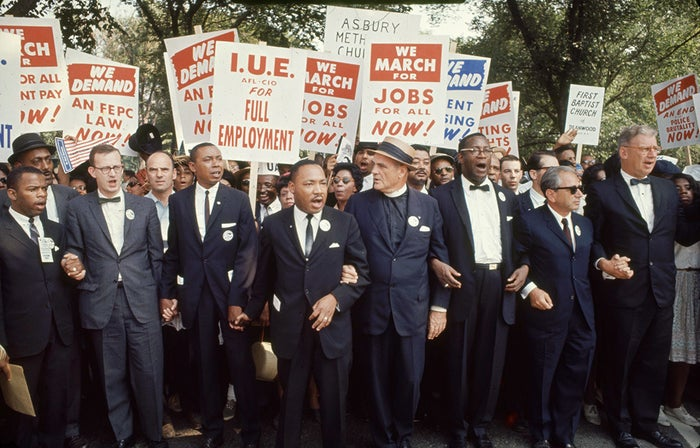 """Leaders of the March on Washington for Jobs & Freedom link arms on Aug. 28, 1963. Among those pictured (front row from left): John Lewis, Matthew Ahman, Floyd B. McKissick, Dr. Martin Luther King Jr., Reverend Eugene Carson Blake, Cleveland Robinson, and Rabbi Joachim Prinz. The march provided the setting for King's iconic """"I Have a Dream"""" speech."""