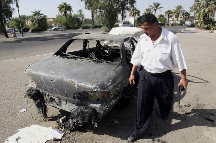An Iraqi traffic policeman inspects a car destroyed on Sept. 16, 2007, by a Blackwater security detail in Nisur Square in Baghdad.