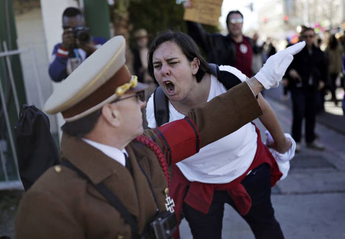 A woman yells at a man dressed as Adolf Hitler.