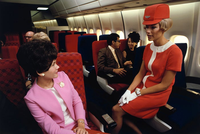 A United Airlines flight attendant talks with a passenger aboard a Douglas DC-10, 1968.
