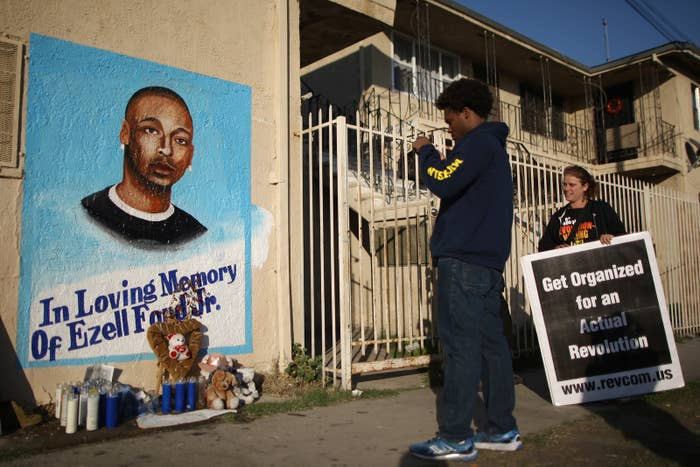 Activists look at a mural of Ezell Ford in December 2014 in Los Angeles.