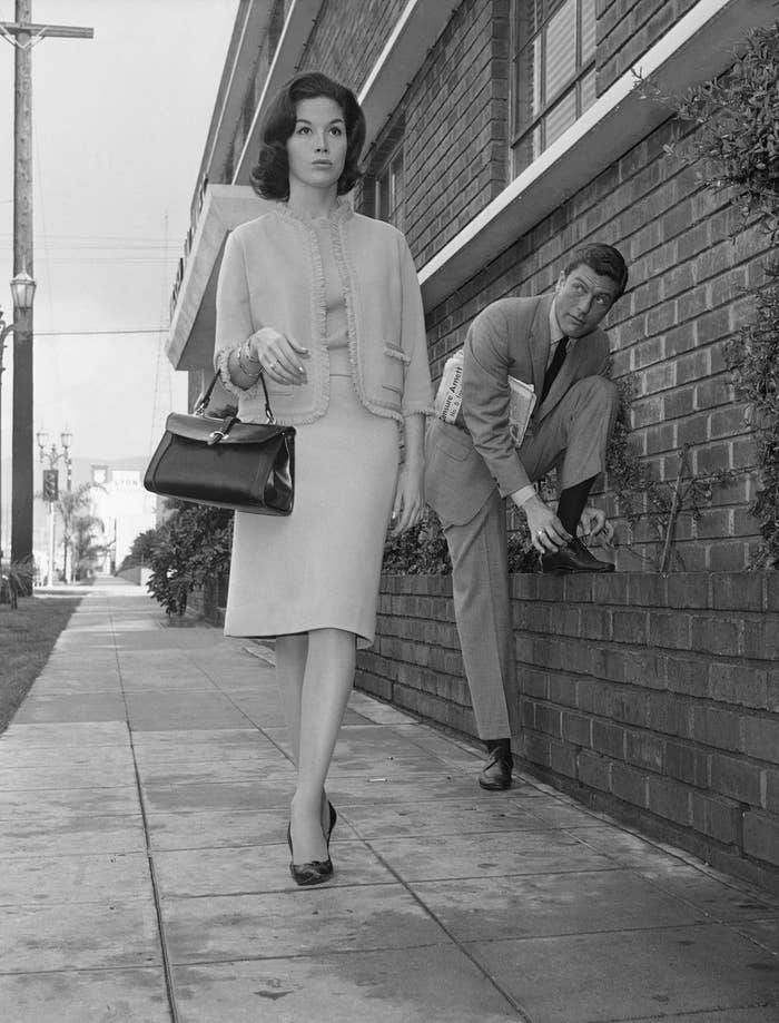 Actor Dick Van Dyke looks on as his co-star Mary Tyler Moore walks by in a publicity still for The Dick Van Dyke Show, Feb. 22, 1962.