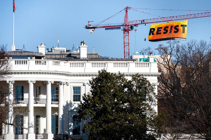 With the White House in the foreground, Greenpeace protesters unfurl a banner atop a crane at the construction site of the former Washington Post office building on Jan. 25 in Washington, DC.
