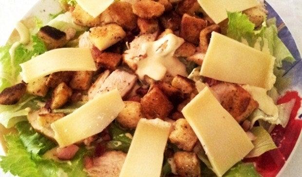 """Você lê """"Salada Caesar"""" e já pensa """"nooooossa"""", mas na verdade ela é mais acessível do que parece. Os ingredientes mais caros são o peito de frango e o bacon (que você pode deixar de fora para ser mais lightzinho): no mais é alface, queijo ralado, maionese e mostarda. Os croutons você pode comprar prontos ou fazer com pão de forma – vale a pena! Veja a receita aqui."""