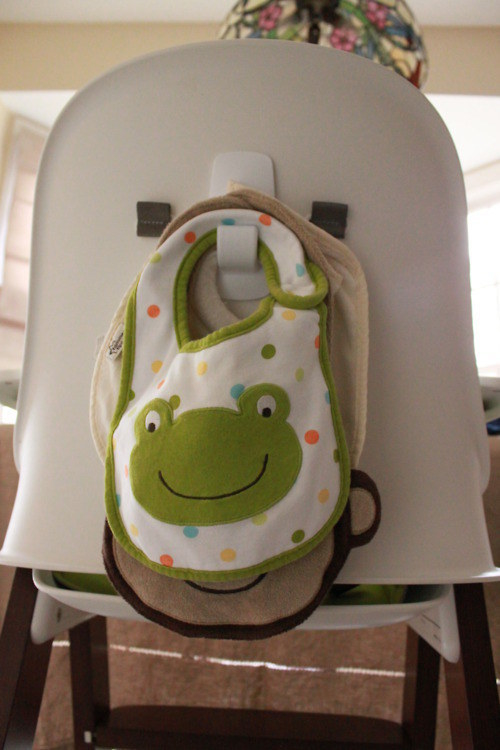 Stick a command hook on the back of a high chair to hang bibs.