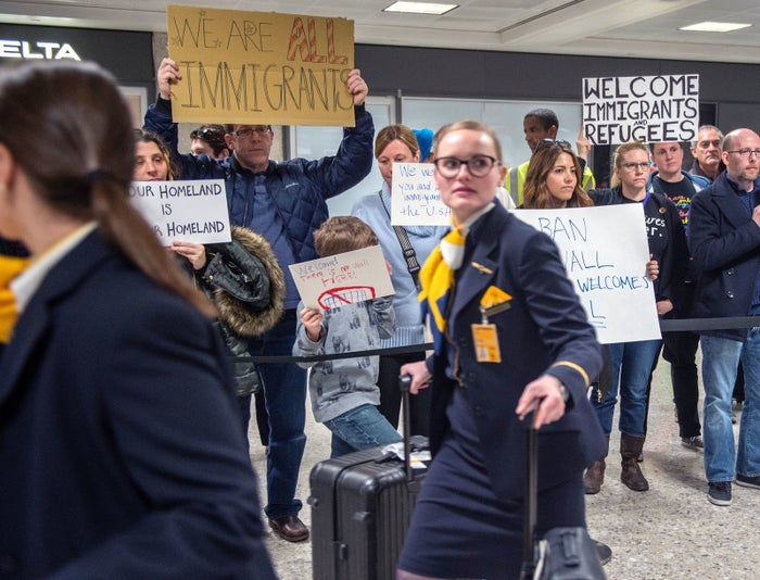 Flight attendants walk past protesters at the international arrivals area of the Washington Dulles International Airport.
