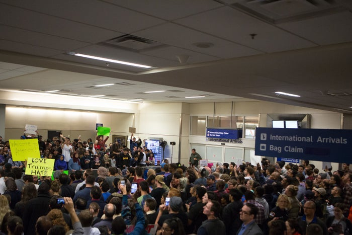 Protesters gather to denounce President Donald Trump's executive order that bans certain immigration, at Dallas-Fort Worth International Airport on January 28, 2017.