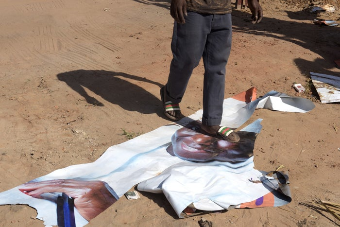 A man walks on a ripped poster from Jammeh's campaign three days after the president lost the election.
