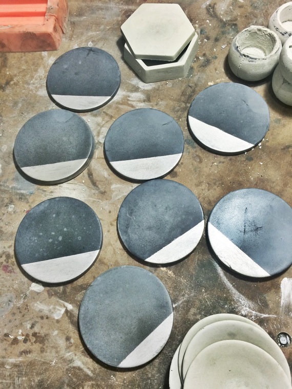Polished charcoal concrete coasters reminiscent of a partial eclipse.