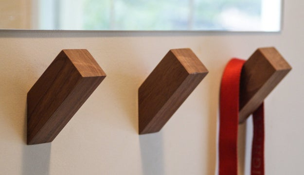 "Slanted walnut or oak wall hooks for the ultimate ""look how little I tried"" storage solution."