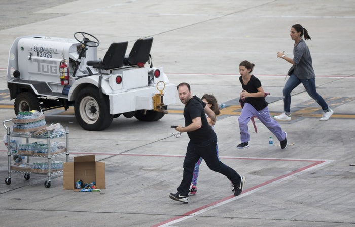 People run on the tarmac at the Fort Lauderdale Airport. Five people were killed during a shooting at the airport on Friday.