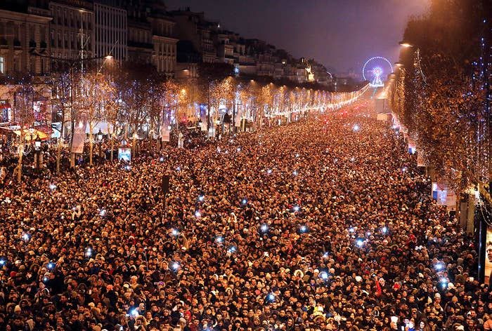 Revellers gather on the Champs Elysees Avenue in Paris, France, during New Year celebrations, late Dec. 31.