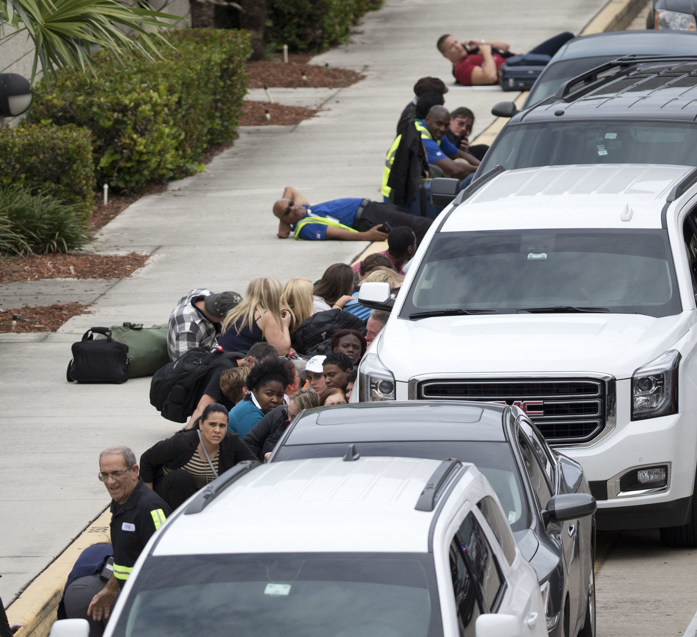 People also sought cover behind cars outside the airport.