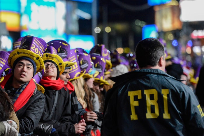 An FBI agent walks past revelers gathered in Times Square on New Year's Eve in New York, U.S. December 31, 2016. REUTERS/Stephanie Keith