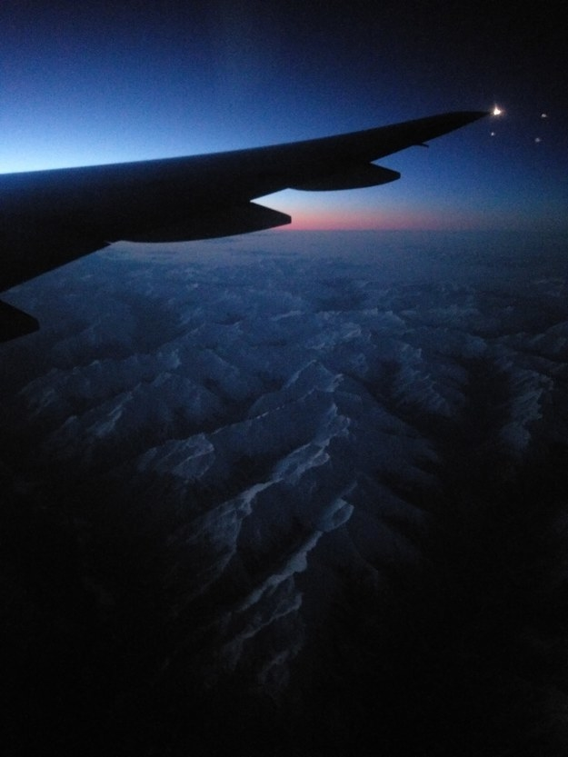 """Flying over the Canadian Rockies before dawn."""