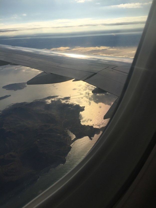 """Flying over San Francisco the Golden Gate Bridge is in the center of the pic."""