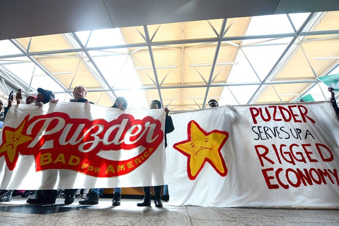 Protesters rally against Labor nominee Andrew Puzder in the lobby of Hardee's Headquarters on February 13, 2017 in St Louis, Missouri.