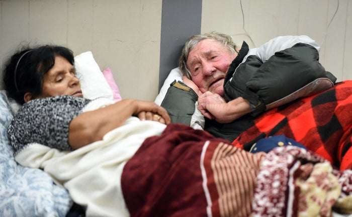 Evacuees Steve Allen (R) and Alicia Castro (L) lay on a cot at the Placer County Fairgrounds evacuation center in Roseville, California.