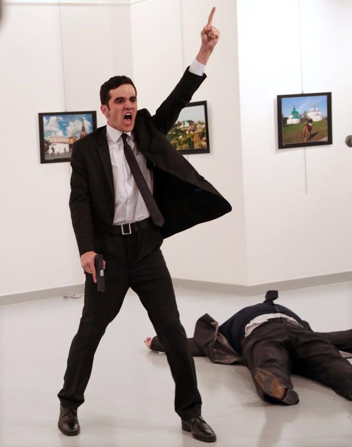 Mevlut Mert Altintas shouts after shooting Andrei Karlov, right, the Russian ambassador to Turkey, at an art gallery in Ankara, Turkey, Monday, Dec. 19, 2016.