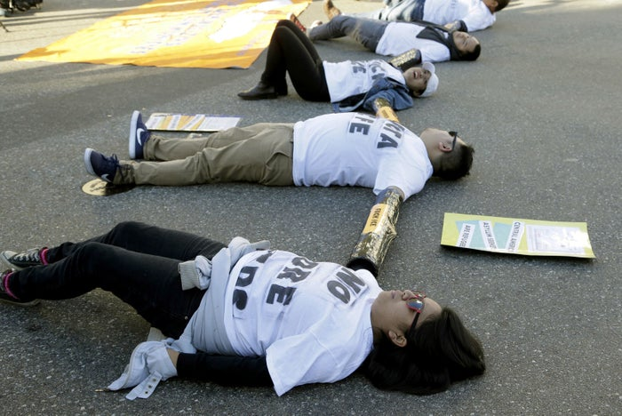 Immigration activists tied together by the arms participate in a sit-in protest against ICE raids and deportations near the downtown Los Angeles Federal Building.