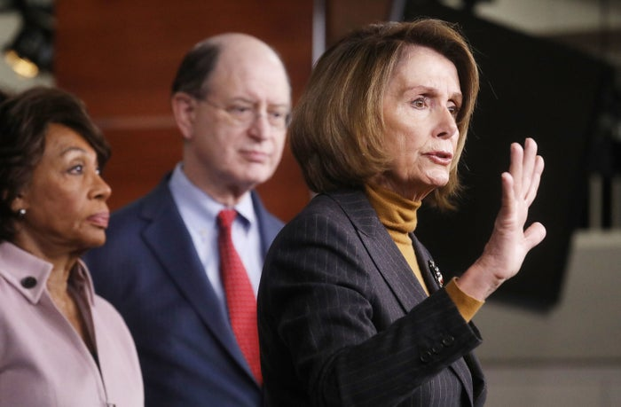 House Minority Leader Nancy Pelosi, Rep. Maxine Waters, and Rep. Brad Sherman stand at a news conference criticizing President Donald Trump's Wall Street policies.