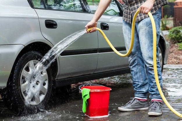 Lavar el coche con manguera.