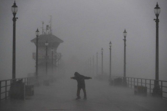 A man struggles against the storm Friday in Huntington Beach, Calif.