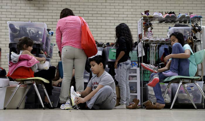 Migrants newly released after processing by ICE officials are fitted for shoes last year in the border city of McAllen, Texas.