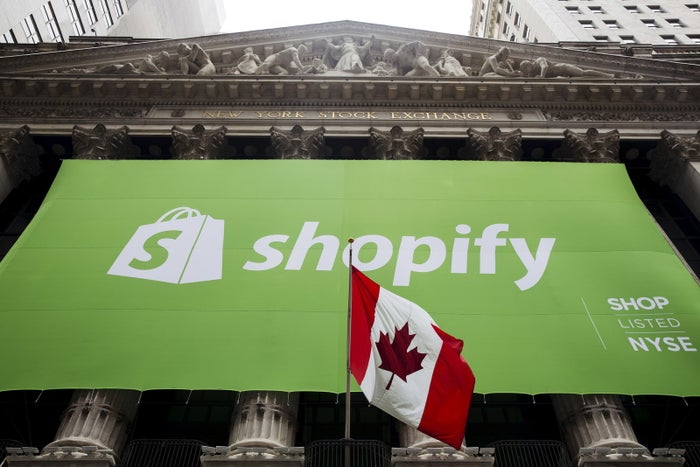 A Shopify banner hangs behind the Canadian flag after the company's IPO at the New York Stock Exchange in 2015.